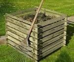 Komposter aus Holz mit Rechen